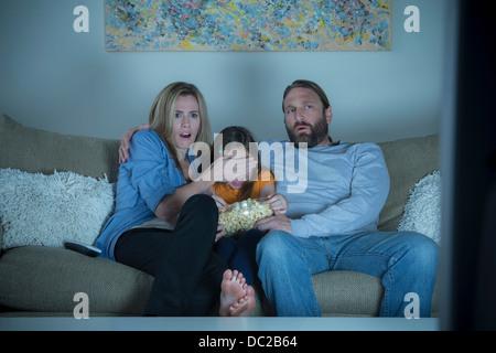 Les parents et l'enfant regardant un film d'horreur Banque D'Images