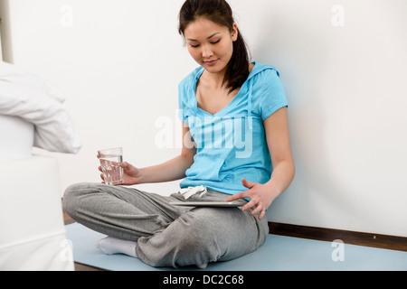Femme assise en tailleur sur le tapis de sol en digital tablet Banque D'Images