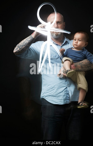 Dessin de l'homme pour divertir bébé dans les bras Banque D'Images
