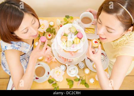 Deux femmes heureux de se livrer à des gâteaux sucrés