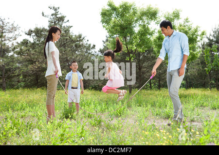 Happy Family jumping rope outdoors Banque D'Images