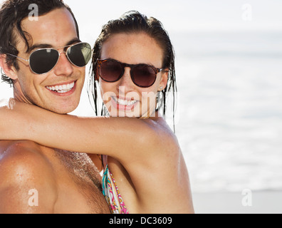 Close up portrait of smiling couple wearing sunglasses on beach Banque D'Images