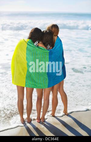 Les amis enveloppés dans des serviettes sur la plage Banque D'Images