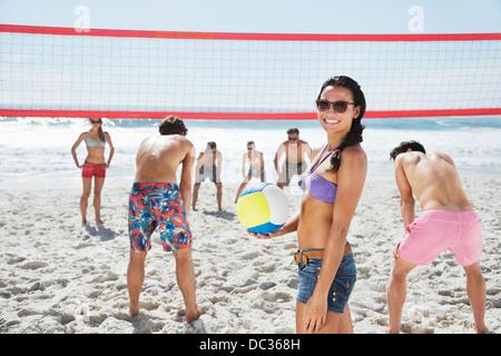 Portrait of smiling woman playing beach-volley avec des amis Banque D'Images