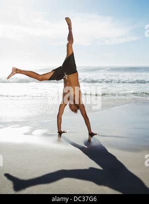 L'homme en maillot de bain doing handstand on beach Banque D'Images
