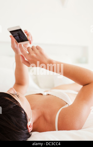 Woman laying in bed using cell phone Banque D'Images
