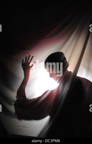 Silhouette d'homme derrière le rideau. La lumière prend le rouge dans sa chemise et la feuille avec reflets lumière Banque D'Images