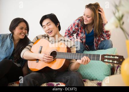 Les jeunes femmes à l'écoute de man playing guitar Banque D'Images