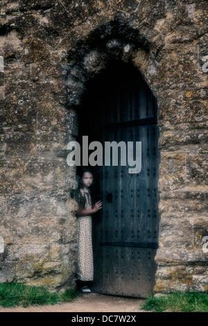 Une fille est à la recherche d'une vieille porte Banque D'Images