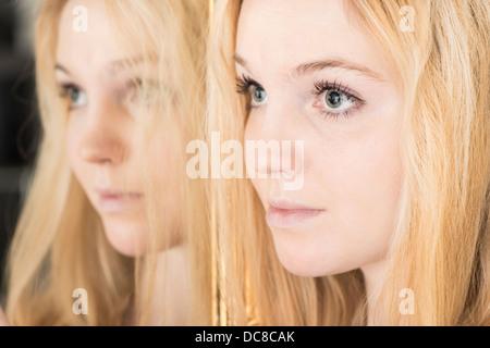 Portrait de jeune femme blonde debout adolescent par mirror à la triste Banque D'Images