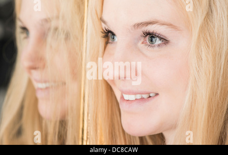 Portrait of happy young blonde female teenager standing by mirror looking away Banque D'Images