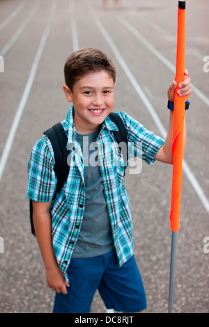 Un garçon se tient et est titulaire d'un brigadier scolaire flag Banque D'Images