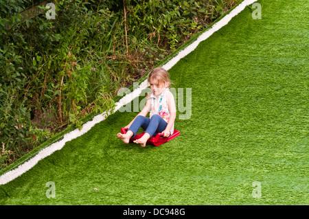 5 ans, fille, glissant sur une colline Banque D'Images