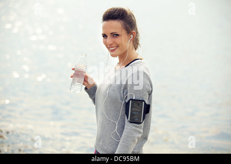 Happy female runner smiling while holding a l'eau en bouteille