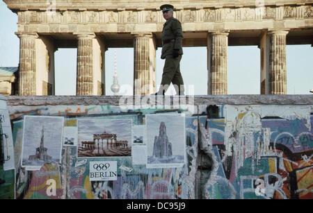 L'ouverture du Mur de Berlin - l'allemand de l'Est garde-frontière de l'ANV est de marcher sur le dessus du mur Banque D'Images