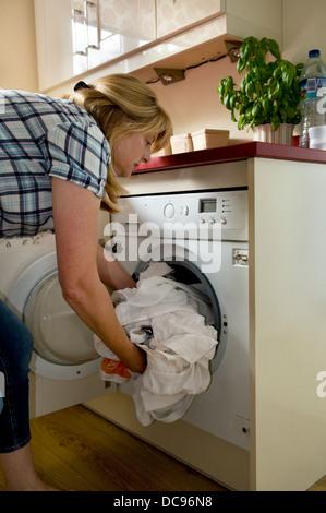 Caucasian woman loading lave-linge à la maison, pris à Bristol, Angleterre, Royaume-Uni Banque D'Images