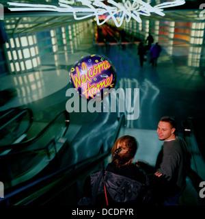 Un jeune homme avec un ballon Accueil Bienvenue, rencontre son partenaire après une longue absence, dans le terminal Banque D'Images