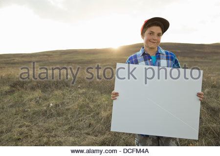 Boy standing on hillside holding blank sign board Banque D'Images