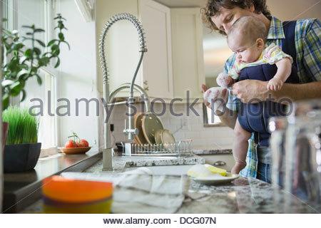 Père holding baby girl tout en lavant la vaisselle Banque D'Images