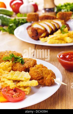 Brochette de poulet frit délicieux sur la plaque blanche sur la table en bois Banque D'Images