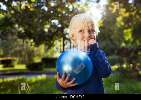Peu cute boy avec la balle jusqu'à la Banque D'Images