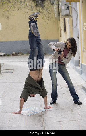 Woman photographing man doing handstand Banque D'Images