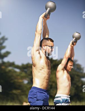 Deux jeunes hommes forts de soulever des poids lourds poids kettlebell Banque D'Images