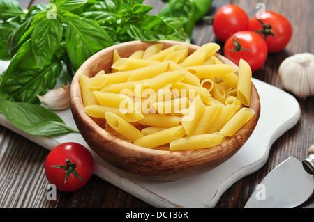 Pâtes penne et tomates au basilic sur planche à découper en bois Banque D'Images
