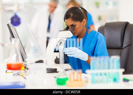 Jeune Indien chercheur médical à par microscope in laboratory Banque D'Images