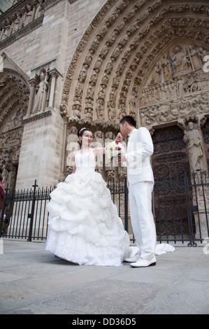 Une asiatique mariés posent pour des photos en face de la cathédrale Notre Dame de Paris. Banque D'Images
