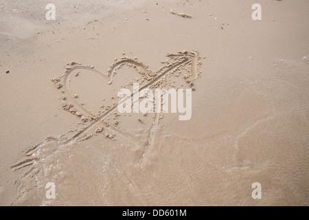Un coeur avec une flèche à travers elle dessiné dans le sable sur une plage. Banque D'Images