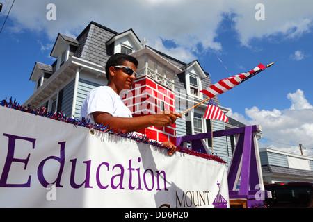 African American boy dans l'université véhicule forme drapeau américain 4 juillet Jour de l'indépendance des défilés, Banque D'Images
