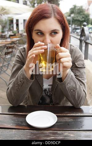 Jeune femme à boire le thé dans un café en plein air Banque D'Images