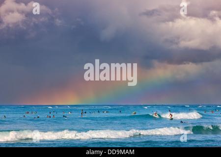 Surfers under the rainbow à la célèbre plage de Waikiki, Honolulu, Oahu, Hawaii Banque D'Images