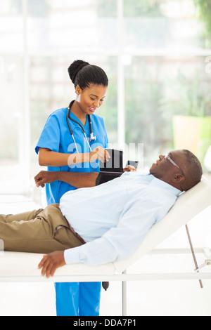 Pretty African female nurse mesurer la pression artérielle senior patient Banque D'Images