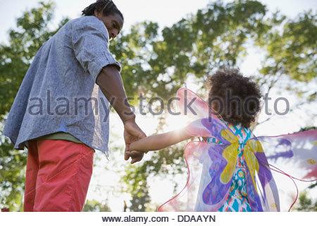 Père et fille holding hands at park Banque D'Images