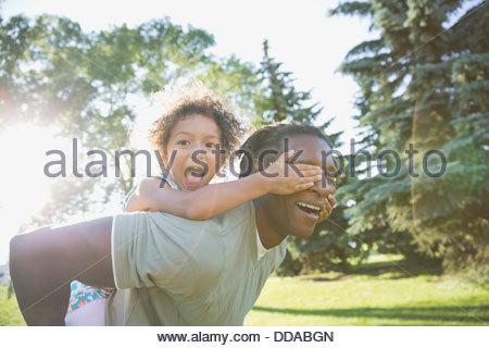 Portrait of playful girl couvrant les yeux des pères dans park Banque D'Images