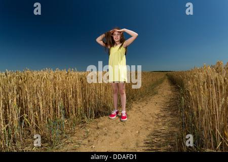 Jeune fille à la recherche autour de dans la campagne ouverte