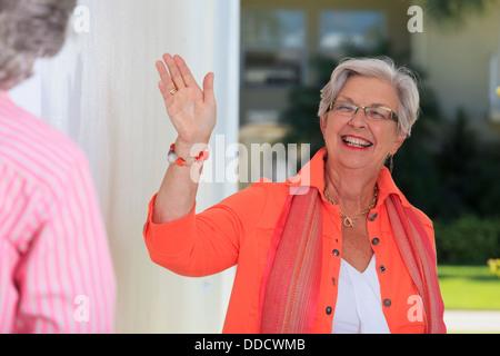 Senior woman waving à son amie Banque D'Images