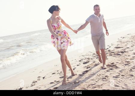 Image dynamique de l'exécution de couple sur la plage. Se tenant la main. Relations sérieuses in Summertime Banque D'Images