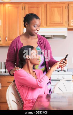 Deux soeurs à la recherche d'un smartphone dans la cuisine, une avec d'apprentissage Banque D'Images