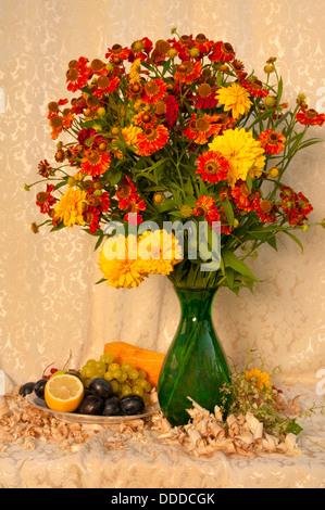 Nature morte avec fleurs jaune vif et orange dans le vase vert avec des fruits