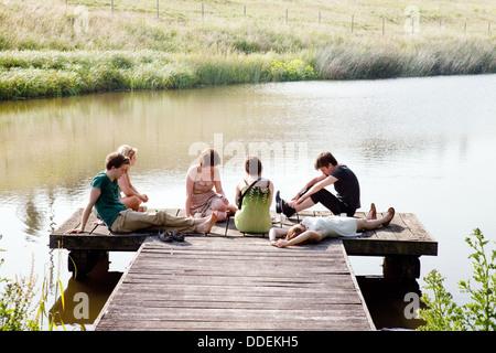 Un groupe d'adolescents assis sur une jetée par un lac en été, Sheepdrove Organic Farm, Lambourn Berkshire, Angleterre, Banque D'Images
