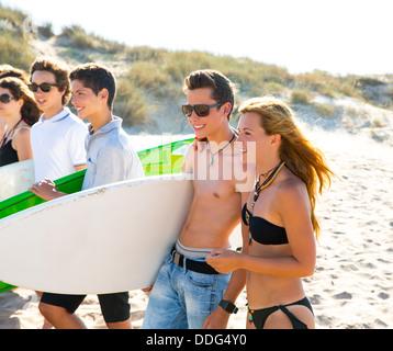 Les garçons et les filles de l'adolescence surfeur group walking on beach sand Banque D'Images