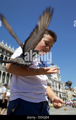 Boy feeding pigeons en plein air sur la place San Marco, Venise Italie