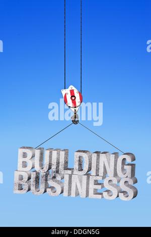 Entreprise de construction dans l'industrie de la construction. Grue de construction béton levage lettres. Banque D'Images