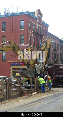 Mettre les travailleurs dans les nouveaux tuyaux sous la rue sur la 7e Avenue à Park Slope, Brooklyn, New York. Banque D'Images