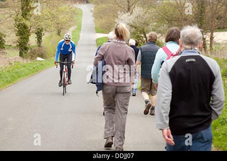 Les gens qui marchent le long d'une route de campagne avec un cycliste passant sur un vélo , Dullingham Cambridgeshire, Banque D'Images