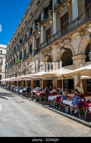 Le café-restaurant en plein air avec les touristes assis dans la Plaza Real ou la Plaça Reial, Barcelone, Catalogne, Espagne Banque D'Images