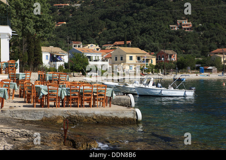 Tables de restaurant en front de mer à Kalami à Corfou, Grèce.Le restaurant est la Maison blanche de l'ancienne Banque D'Images